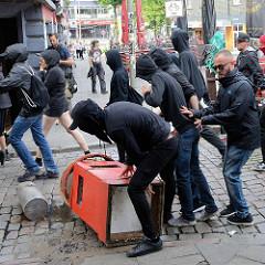 Der sogen. Schwarze Block beim Protest gegen den G 20 Gipfel in Hamburg; eine Barrikade wird errichtet.
