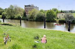 Sommertag in Hamburg Wilhelmsburg - Menschen im grünen Gras vom Deich am Ernst August Kanal - ein rotes Kanu fährt auf dem Wasser.