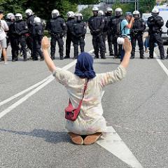 Colour the Red Zone - Protest gegen den G 20 Gipfel in Hamburg, eine Demonstrantin sitzt alleine vor einer Polizeikette und hebt die Arme.