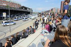 Sitzplätze am Baumwall - Hafenpromenade; Interessierte schauen dem Aufmarsch der Polizeiwagenkolonnen während der Proteste gegen den G20 Gipfel in Hamburg zu.