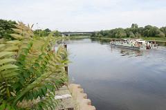 Stillgelegte Kai- Hafenanlage in Riesa an der Elbe - das Arbeitsschiff Elbegrund vom Wasser- und Schifffahrtsamt Magdeburg fährt elbabwärts.