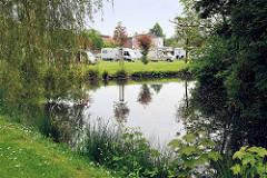 Stellplatz für Wohnmobile an dem historischen Umfassungsgraben einer Gartenanlage in der Stadt Wilster.