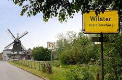 Ortsschild Wilster, Kreis Steinburg - im Hintergrund die Rumflether Mühle, erbaut 1872 als Galerie-Holländer.