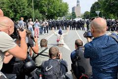 Fotografen bei der Arbeit beim Protest gegen den G 20 Gipfel in Hamburg, eine Demonstrantin sitzt alleine vor einer Polizeikette und hebt die Arme.