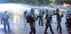 Polizisten in Kampfmontur rücken im Schutz eines Wasserwerfers im Schanzenviertel gegen den Protest vor -  in der Bildmitte noch ausharrende Demonstranten.