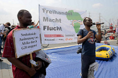 Sprecher und Transparente gegen den G 20 Gipfel in Hamburg; neokoloniale Ausbeutung von Afrika durch G20 - Freihandel Macht Flucht.