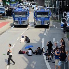 Colour the Red Zone - Protest gegen den G 20 Gipfel in Hamburg, Demonstranten ruhen sich im Schatten auf der Straße aus - Wasserwerfer stehen zur Abkühlung bereit.