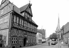 Altes Rathaus von Wilster, historische Fachwerkarchitektur der Renaissance, erbaut 1585 - im Hintergrund der Kirchturm der St.-Bartholomäus-Kirche.