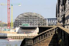 Blick über die Norderelbe zum Kirchenpauerkai und der Baustelle / Stahlkonstruktion vom Bahnhof Elbbrücken; re. die Freihafenelbbrücke mit einem historischen Treppenabgang / Steintreppe mit Treppengeländer, Säulen.