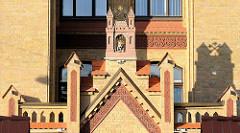 Gelbe Ziegel mit roten Zierkeramikbänder - gegenständliches Wappen von Riga; Gebäude der Klinik.