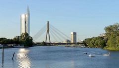 Altes Hafenbecken an der Daugava / Düna in Riga; Nutzung für Wasserski; im Hintergrund das Bürohochhaus der  Zentrale der Swedbank, erbaut 2004 - Architekt Saules Akmens, daneben die Vanšu-Brücke