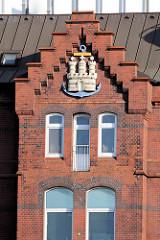 Hamburger Hafenwappen am Giebel / Fassade eines historischen Backsteingebäudes auf dem Werftgelände von Blohm + Voss in Hamburg Steinwerder.