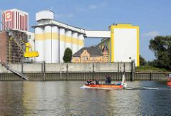 Industriearchitektur am Reiherstieg - Kaimauer und Silos; Gründerzeitvilla mit gelber Ziegelfassade; Motorboot der Feuerwehr.