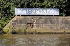 Kaimauer und altes blaues Hafenschild mit Namen des Hafenbeckens Moldauhafen im Hamburger Hafen.