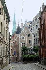 Enge Strassen mit Kopfsteinpflaster - historische Architektur in Riga; im Hintergrund der Kirchturm der St. Jakobi Kathedrale.
