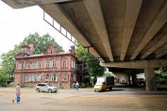 Betonkonstruktion einer Autobrücke in Riga - historisches Wohnhaus.