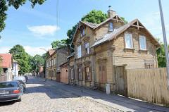 Straße mit Kopfsteinpflaster - alte Holzhäuser / Holzarchitektur in Riga / Lettland.