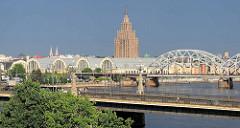 Abendstimmung in Riga - Brücken über die Daugava/ Düna ; re. die alten Zeppelinhallen, jetzt Markthallen - re. die sowjetische Architektur vom Gebäude der Akademie für Wissenschaft - davor die Eisenbahnbrücke.