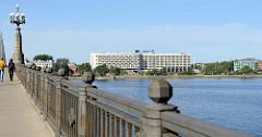 Autobrücke / Fussgängerbrücke über die Daugava / Düna in Riga, Hauptstadt Lettlands - Hotelgebäude am Flussufer.