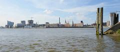 Blick von der Einfahrt des Moldauhafens über die Norderelbe zum Strandkai und der Hamburger Hafencity - re. eine alte Holzdalbe und das Veddelhöft, lks. die Elbphilharmonie.