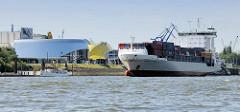 Der Containerfeeder Henneke Rambow läuft in den Hamburger Hafen ein; am Ufer die Gebäude vom Theater an der Elbe und dem Theater Hafen Hamburg; am Ponton der Museumsdampfer Schaarhörn.