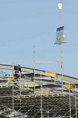 Arbeit an den  Stahlträger vom Dach des Hamburger Bahnhofs Elbbrücken - ein Kran bringt neue Glasplatten für die Verglasung der Dachkonstruktion.