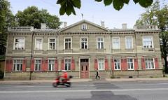 Wohngebäude mit Holzfassade und Fensterläden - Steinbalustrade mit Säulen auf dem Dach; Architekturfotos aus Riga / Lettland.