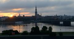 Sonnenaufgang über der Altstadt von Riga - Blick über die Düna, Kirchturm der Petrikirche.