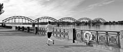 Flusspromenade in Riga - Jogger, altes Eisengeländer - Eisenbahnbrücke,  Stabbogenbrücke, Fachwerkbogenbrücke - erbaut 1914.