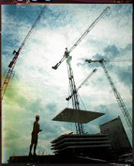 Baukräne und Bauarbeiter auf einer Baustelle in der Hamburger Hafencity.