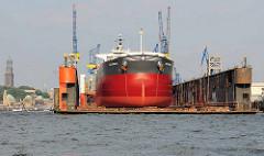 Massengutfrachter Delphinus im Schwimmdock der Hamburger Werft Bloh + Voss - im Hntergrund die St. Pauli Landungsbrücken und die St. Michaeliskirche.