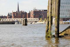 Alter, vermoderter Holzdalben mit Wildkraut am Veddelhöft; im Hintergrund die Baakenbrücke und die Einfahrt zum Magdeburger Hafen in Hamburg.