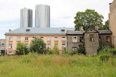 Alte Wohnhäuser, verlassenes / verfallenes Holzhaus in Riga - dahinter die Z-Towers / Hochhäuser, Wohngebäude.
