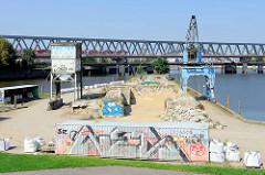 Blick zur Kaianlage mit Schüttgut am Billhafen in Hamburg Rothenburgsort; eine S-Bahn fährt über die Brücke am Oberhafenkanal.