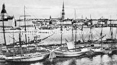Historische Aufnahme vom Hafen in Riga; Segelschiffe in einem Hafenbecken - Blick zur Altstadt von Riga, Ufer der Düna - Petrikirche und Rigaer Dom.
