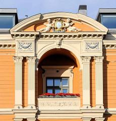 Klassizistische Architektur - Balkon mit kannelierten Säulen; Putten tragen ein Monogramm - Architektur in Riga, Hauptstadt Lettlands.