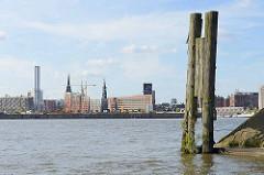 Blick von der Einfahrt des Moldauhafens über die Norderelbe zum Strandkai und der Hamburger Hafencity - re. eine alte Holzdalbe und das Veddelhöft.