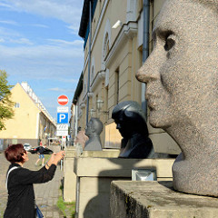 Historisches Verwaltungsgebäude in Riga - Steinskulpturen / Büsten stehen auf Sockeln.