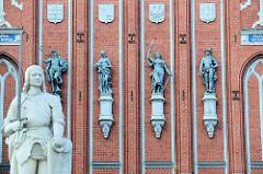 Fassade vom Schwarzhäupterhaus  auf dem Rathausplatz der lettischen Hauptstadt Riga;  Skulpturen des Neptun, die Allegorien der Eintracht und des Friedens und die Skulptur des Merkurs und die Stadtwappen der Hansestädte Riga, Bremen, Lübeck und Ha