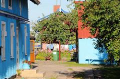 Blumengarten, Wäschetrockenplatz zwischen bunten Holzhäusern in Nida, Kurische Nehrung Litauen.
