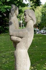Steinskulptur Mutter mit Kind in der Grünanlage vor der Kirche Zum Guten Hirten in Hamburg Stellingen / Langenfelde.