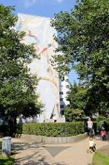 Wandbild an der Fassade eines Hochhauses in der Lenzsiedlung von HH-Lokstedt;  Wir alle - eine Welt / Riesenwandbild - Nushin Morid, Kai Teschner 2004.