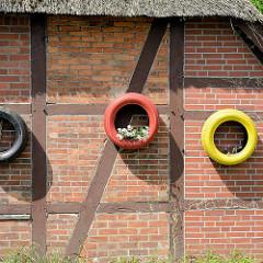 Schwarz - rot - gold, Autoreifen als Pflanzbehältnis - Fachwerkhaus mit Reetdach in Stelle.