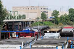 Arbeitsschiffe im Travehafen, dahinter die Travehafenbrücke, die ehem. Einfahrt zum Ellerholzkanal; dahinter ein Verwaltungsgebäude vom ehem. Buss-Hansa-Terminal, dessen Betrieb Ende 2016 eingestellt wurde.
