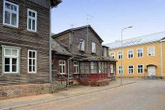 Historische Architektur in Fellin / Viljandi, Estland; alte Häuser mit Veranda, rohe Holzfassade, Fundament mit Findlingen - im Hintergrund ockerfarbenes Wohnhaus.