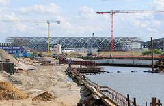 Baustelle am Baakenhafen in der Hamburger Hafencity - im Hintergrund die Glas- / Stahlkonstruktion der entstehenden Haltestelle / Bahnhof Elbbrücken.