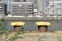 Blick zu den Baustellen am Versmannkai im Hamburger Baakenhafen; im Vordergrund Eisenpoller / Wildkraut am Petersenkai.