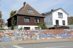 Wohnhäuser an der Volksparkstrasse in Hamburg Stellingen - alte Ziegelmauer mit abgeblättertem Putz, Grafitti HSV supporter.