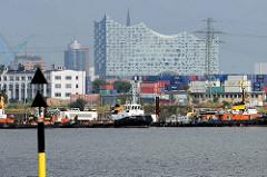 Blick vom Sthamerkai über den Oderhafen zum Ellerholzhafen im Hamburger Hafengebiet. Schlepper in unterschiedlicher Größe liegen am Kai bei der Buchheisterstraße, dahinter das hoch aufragende Gebäude der Elbphilharmonie.