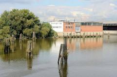 Panorama vom Moldauhafen im Hamburger Stadtteil Kleiner Grasbrook; lks, der Lagerschuppten G, in der Bildmitte Lagergebäude vom Übersee Zentrum; alte Holzdalben stehen im Hafenbecken.